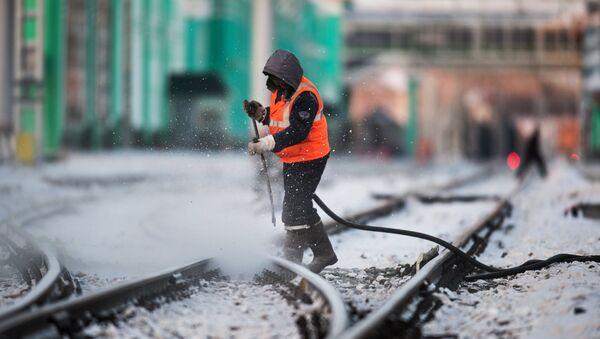 Радник чисти пругу на железничкој станици у Омску - Sputnik Србија