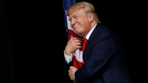 Donald Tramp grli američku zastavu na mitingu u Tampi - Sputnik Srbija