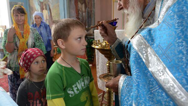 Seoski sveštenik pričešćuje decu - Sputnik Srbija