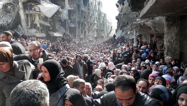 Палестинске избеглице и становници опкољеног избегличког кампа Јармук у близини Дамаска, стоје у реду за хуманитарну помоћ - Sputnik Србија