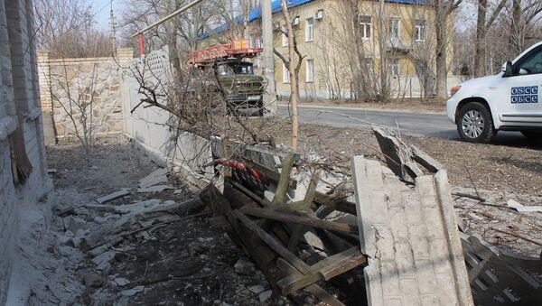 Vozilo delegacije OEBS-a u blizini kuće oštećene u granatiranju u Donjeckoj oblasti. - Sputnik Srbija