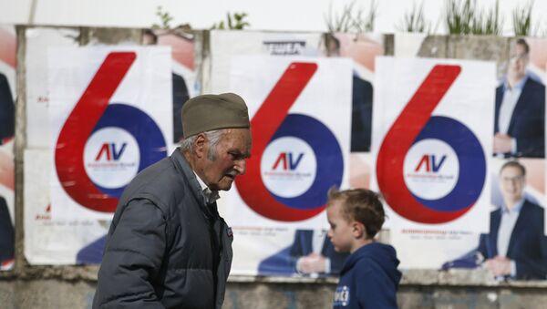 Čovek šeta pored plakata Aleksandra Vučića - Sputnik Srbija