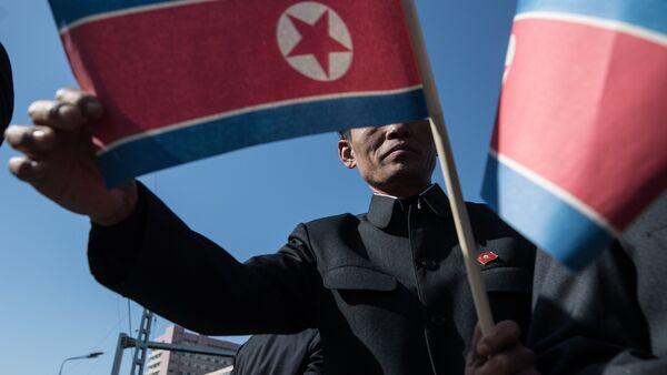 Становник носи заставу Северне Кореје на свечаности отварања новог стамбеног комплекса у Пјонгјангу - Sputnik Србија