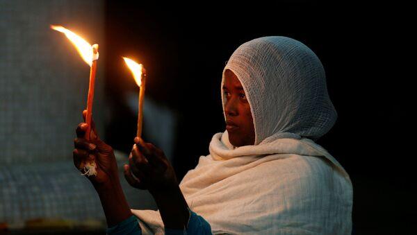 Етиопска православна верница током вечерње ускршње молитве у цркви Медхане Алем у Адис Абеби, Етиопија - Sputnik Србија