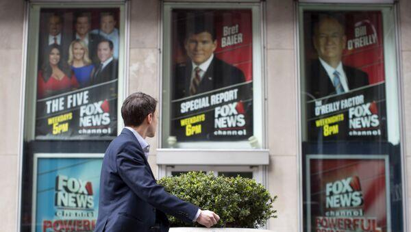 Човек пролази поред седишта компаније Њуз на којој су налепљени постери са ликом бившег новинара телевизије Фокс Њуз Била О'Рајлија - Sputnik Србија