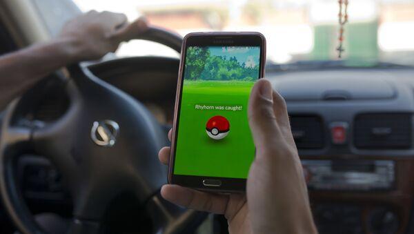Čovek igra Pokemon go dok vozi automobil. - Sputnik Srbija