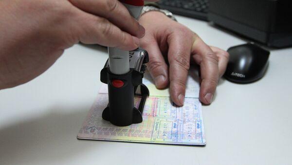 Pripadnik beloruske pogranične službe stavlja pečat u pasoš na belorusko-poljskoj granici - Sputnik Srbija