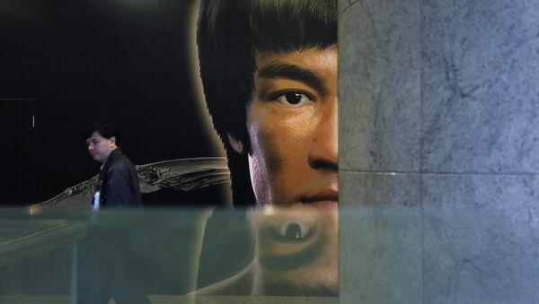 Човек пролази поред постера за Брус Лијеву изложбу у Хонг Конгу. - Sputnik Србија
