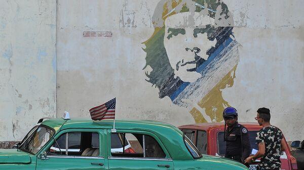 Аутомобил пролази поред графита са ликом Ернеста Че Геваре у Хавани на Куби - Sputnik Србија