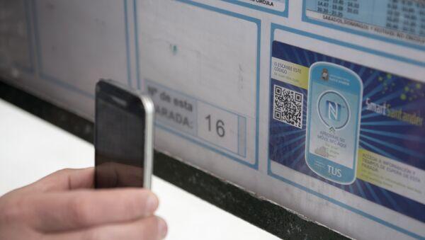 Човек користи мобилни телефон да би очитао код за паметну налепницу на аутобуском стајалишту у Сантандеру. Паметна налепница пружа информације о реду вожње градског превоза - Sputnik Србија