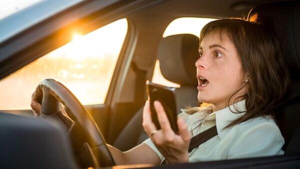 Девојка држи телфон док вози - Sputnik Србија