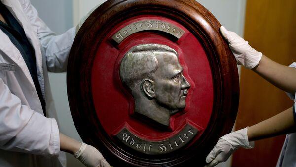 Федерални полицајци показују портрет Адолфа Хитлера у седишту Интерпола у Буенос Ајресу. - Sputnik Србија