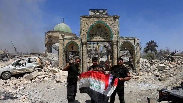 Pripadnici iračkih protivterorističkih snaga sa zastavom Iraka ispred ruševina velike džamije Nuri u Mosulu - Sputnik Srbija