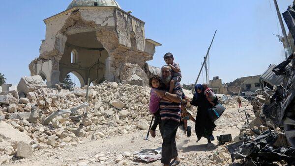 Irački civili pored oštećene džamije Nuri tokom ofanzive iračkih snaga protiv militanata DAEŠ-a u Mosulu - Sputnik Srbija