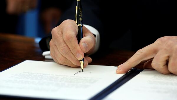 Амерички председник Доналд Трамп потписује документа у Овалном кабинету - Sputnik Србија