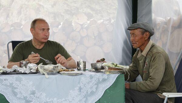 Владимир Путин на одмору пије чај са мештанином села у Туви. - Sputnik Србија