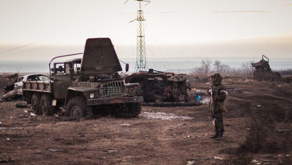 Dobrovoljac Donjecke Narodne Republike u naselju Logvinovo u Donbasu pored uništene ukrajinske vojne tehnike - Sputnik Srbija
