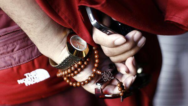 Рука тибетанског монаха са сатом, бројаницом и ајфоном - Sputnik Србија