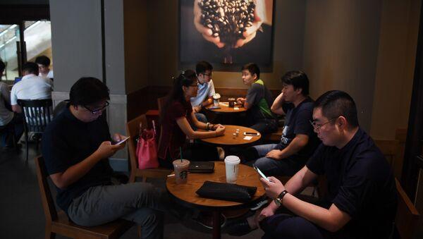Људи седе у кафићу у Пекингу - Sputnik Србија