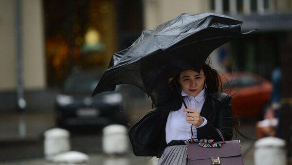 Девојка се штити кишобраном током кише у Москви - Sputnik Србија