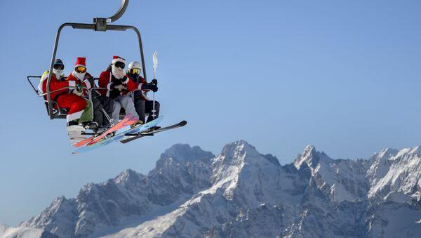 Људи у костимима Деда Мраза возе се ски лифотом у швајцарским Алпима. - Sputnik Србија