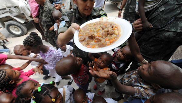 Brazilski mirovnjaci UN dele hranu siročićima na Haitiju. - Sputnik Srbija