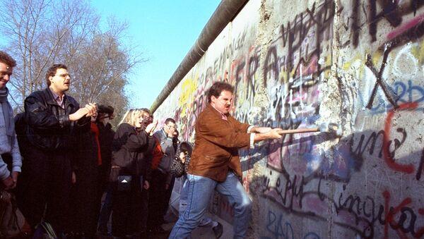 An unidentified West Berliner swings a sledgehammer, trying to destroy the Berlin Wall near Potsdamer Platz, on November 12, 1989, where a new passage was opened nearby - Sputnik Србија