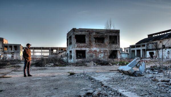 Čovek u uništenoj fabrici. - Sputnik Srbija
