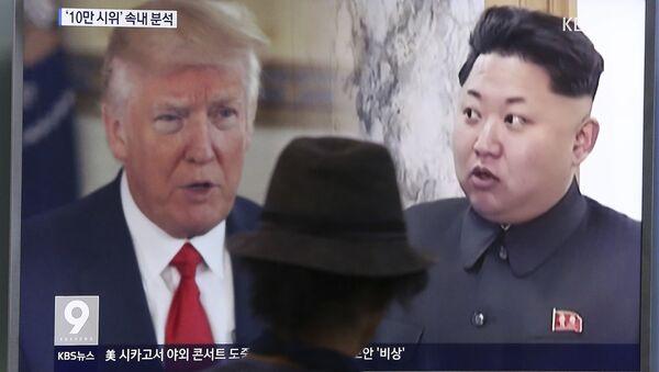 Čovek gleda ekran na kome su predsednici SAD i Severne Koreje Donald Tramp i Kim Džong Un, na železničkoj stanici u Seulu. - Sputnik Srbija