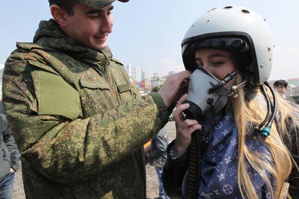 Vojnik pomaže devojci da stavi pilotsku kacigu na Sajmu vojne tehnike u Vladivostoku - Sputnik Srbija