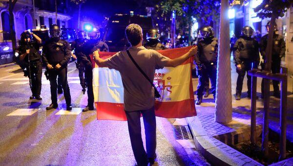 Pristalica ujedinjenja sa zastavom Španije stoji ispred katalonske regionalne policije u Barseloni - Sputnik Srbija