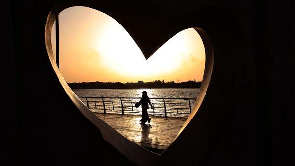 Saudi woman seen through a heart-shaped statue walks along an inlet of the Red Sea in Jiddah, Saudi Arabia - Sputnik Србија