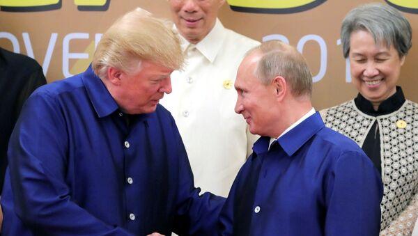 Председник САД и Русије Доналд Трамп и Владимир Путин рукују се на церемонији фотографисања лидера самита АПЕК-а у Вијетнаму - Sputnik Србија
