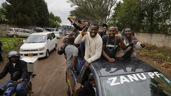 Хиљаде Зимбабвеанаца преплавило је данас улице Харареа, машући националним заставама уз песму и плес, усхићено очекујући пад председника Роберта Мугабеа. - Sputnik Србија