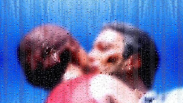 Muškarac i žena ljube se dok kiša pada na prozor - Sputnik Srbija