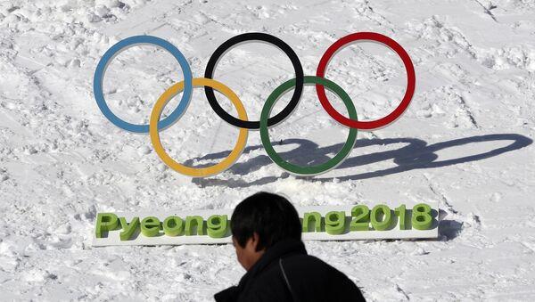 Човек пролази поред олимпијских кругова за ОИ 2018. у Пјонгчангу - Sputnik Србија