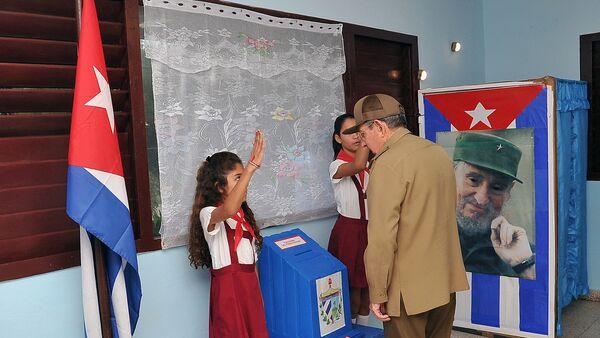 Predsednik Kube Raul Kastro glasa na lokalnim izborima u Havani, ispred fotografije njegovog brata, Fidela Kastra 26. novembra 2017. - Sputnik Srbija