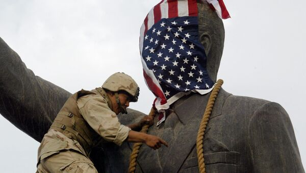 Амерички маринац покрива главу статуе ирачког председника Садама Хусеина америчком заставом пре њеног рушења у Багдаду, 9. април 2003. - Sputnik Србија
