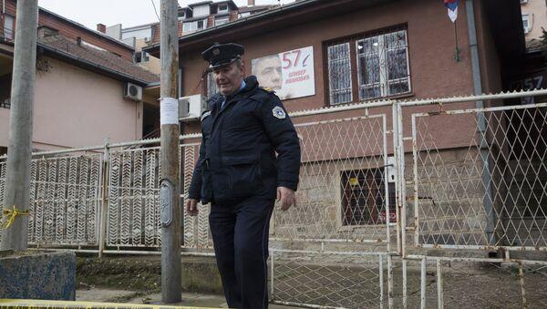 Kosovski policajac ispred kuće gde je ubijen Oliver Ivanović u Kosovskoj Mitrovici. - Sputnik Srbija