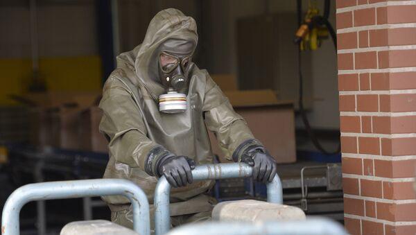 Stručnjak za hemijsko oružje sa gas-maskom sakuplja uzorke sa mesta navodnog hemijskog napada - Sputnik Srbija