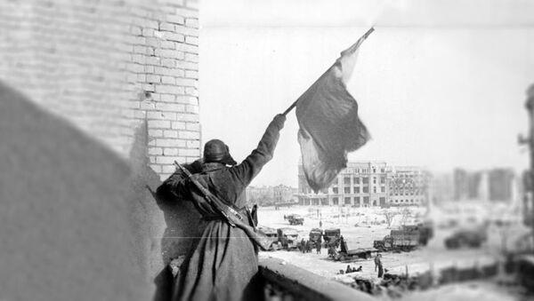 Совјетски војник  маше црвном заставом над централним тргом Стаљинграда 1943. - Sputnik Србија