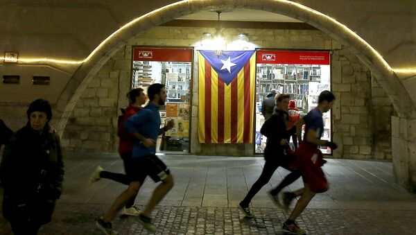 Људи трче поред заставе Каталоније - Sputnik Србија