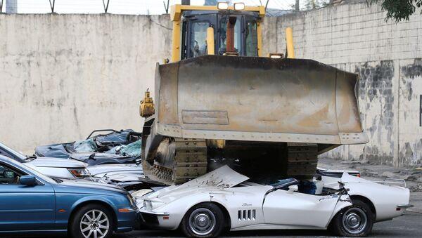Булдожер уништава заплењене аутомбиле на паркингу - Sputnik Србија