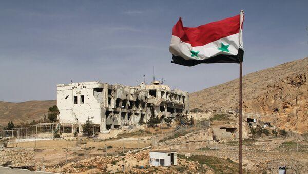 Sirijska zastava ispred porušene kuće u gradu Malula, 55 kilometara od Damaska, koju su dva puta pljačkali teroristi Nusra fronta - Sputnik Srbija