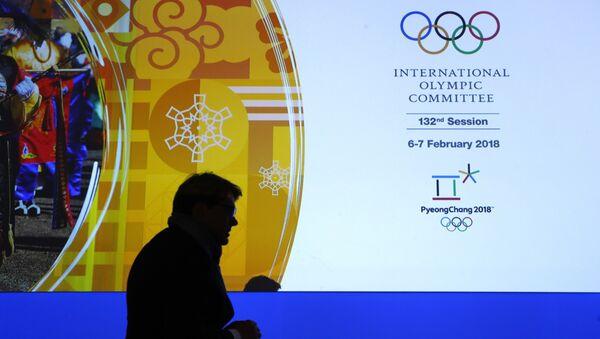 Član Međunarodnog olimpijskog komiteta prolazi pored displeja sa logom MOK-a na Zimskim olimpijskim igrama u Pjongčangu - Sputnik Srbija