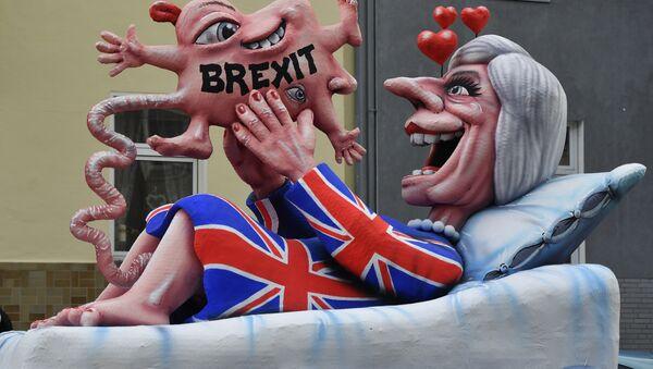 Maskota koja ismeva britansku premijerku Terezu Mej koja gleda svoju bregzit bebu na paradi u Deseldorfu. - Sputnik Srbija