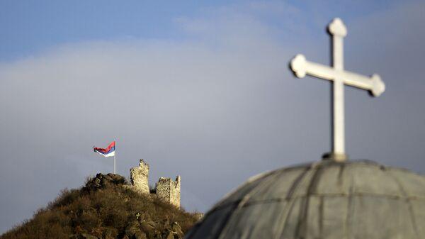 Српска застава поред остатака средњевековног града и Црква Светог Ђорђа у Северној Митровици - Sputnik Србија