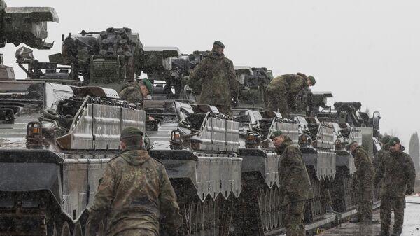 Припадници немачке војске, део НАТО контингента, истоварују војна возила у Литванији - Sputnik Србија