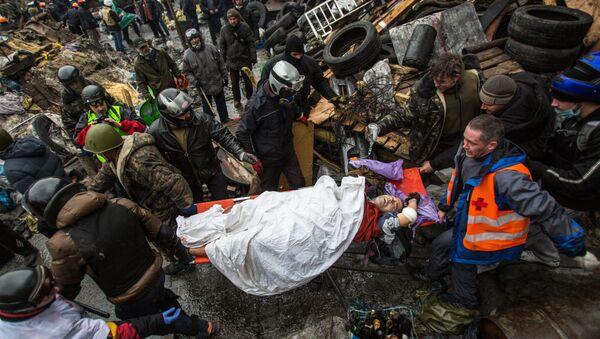 Pristalice opozicije nose ranjenika tokom sukoba demonstranata i pripadnika policije na Trgu nezavisnosti u Kijevu 20. februara 2017. - Sputnik Srbija