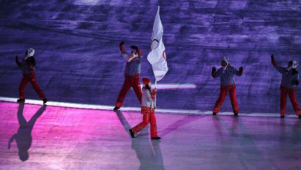Волонтер носи олимпијску заставу под којом наступају руски спортисти на Олимпијским играма у Пјонгчангу 2018. - Sputnik Србија